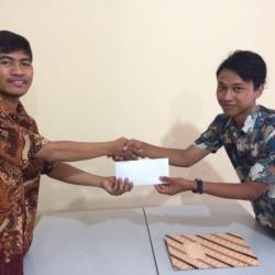 Serah terima antara Pulung Nursiyanta selaku Ketua Komunitas Belajar Sedekah (kiri) dengan Tri Setyo Dermawan (kanan)