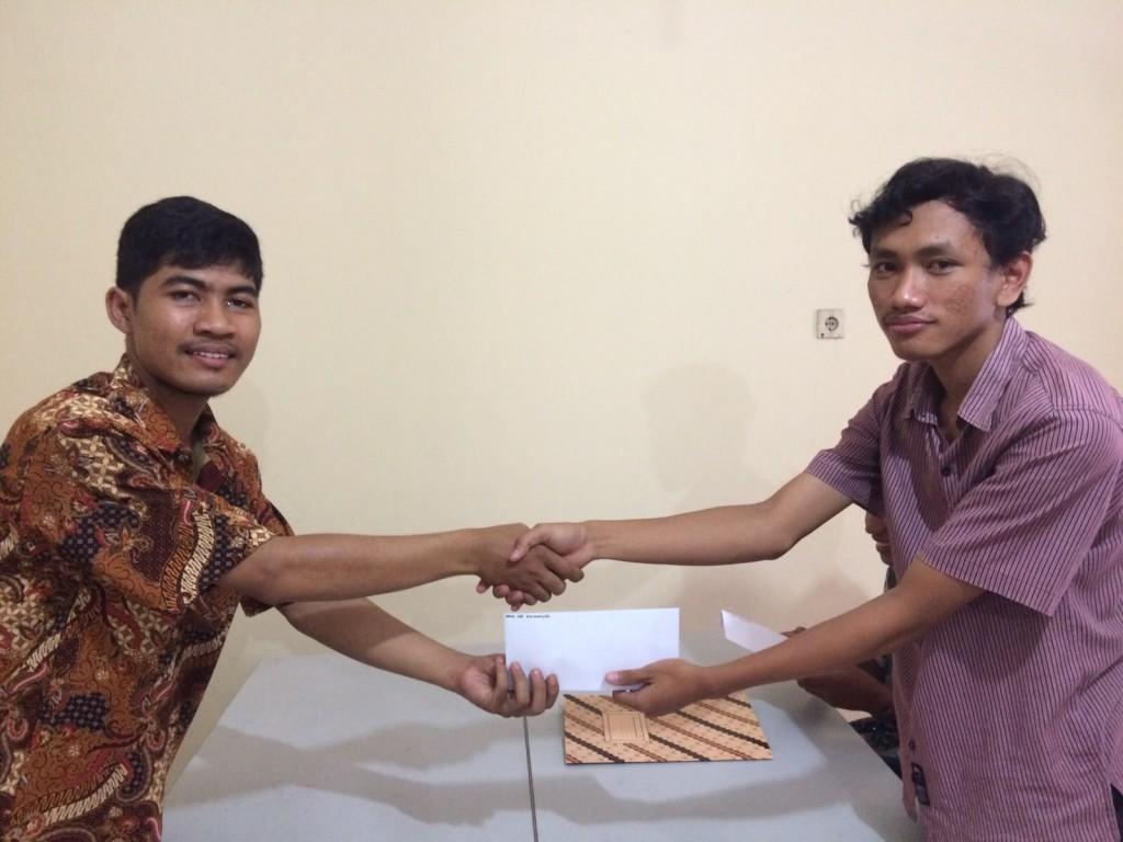 Serah terima antara Pulung Nursiyanta selaku Ketua Komunitas Belajar Sedekah (kiri) dengan Iqbal Adi N. (kanan)